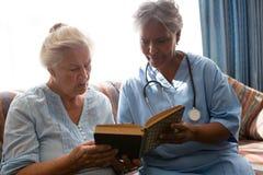 Docteur avec le livre de lecture supérieur de femme tout en se reposant sur le sofa Image stock