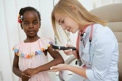 Docteur avec le matériel médical aidant peu de fille photos libres de droits