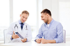 Docteur avec le PC et le patient de comprimé dans l'hôpital photographie stock