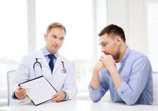 Docteur avec le presse-papiers et le patient dans l'hôpital photo stock