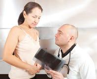 Docteur avec le rayon X de regard patient Photographie stock libre de droits