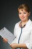 Docteur avec le stéthoscope et l'électrocardiogramme Photographie stock libre de droits
