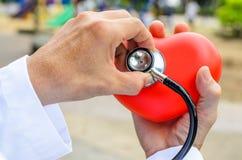 Docteur avec le stéthoscope examinant le coeur rouge Image stock