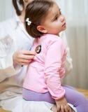 Docteur avec le stéthoscope examinant une fille d'enfant image stock