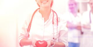 Docteur avec le stéthoscope tenant le coeur, d'isolement sur le fond blanc photos libres de droits