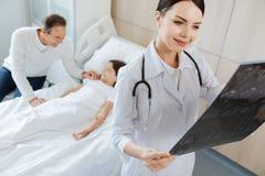 Docteur avec plaisir agréable tenant une photo de rayon de X Photographie stock libre de droits