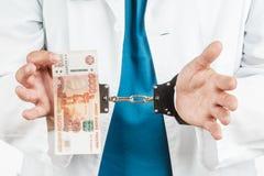 Docteur avec un stéthoscope et 5000 billets de banque et menottes un Cr Photographie stock