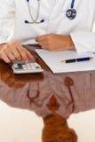 Docteur avec une calculatrice. Pratique en matière médicale de calcul des coûts photo stock