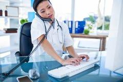 Docteur ayant l'appel téléphonique et à l'aide de son ordinateur Images libres de droits
