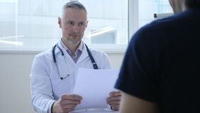 Docteur bouleversé Discussing Medical Papers avec le patient photo stock