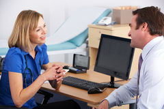 Docteur BRITANNIQUE de femelle parlant au patient mâle Photographie stock