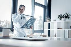 Docteur calme sérieux tenant le balayage et appeler de rayon X Photo libre de droits