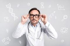 Docteur calme touchant ses verres et semblant attentif photos libres de droits