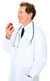 docteur caucasien de pomme mangeant l'aîné d'isolement Photographie stock