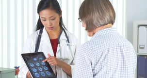 Docteur chinois parlant au patient au sujet des rayons X photo libre de droits