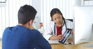 Docteur chinois passant en revue le rayon X avec le patient images libres de droits