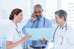 Docteur concentré montrant le dossier à ses collègues tout en appelant image libre de droits