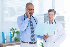 Docteur concentré montrant le dossier à son collègue tout en appelant Images stock