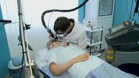Docteur conduisant le retrait de laser de la pigmentation banque de vidéos