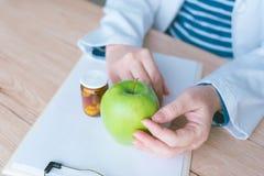 Docteur conseillant la pomme au lieu des pilules et des antibiotiques photo stock
