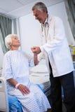 Docteur consolant le patient supérieur dans la salle Image stock