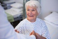 Docteur consolant le patient supérieur dans la salle Photo libre de droits