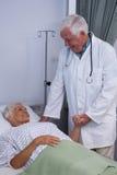 Docteur consolant le patient supérieur dans la salle Photo stock