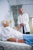Docteur consolant le patient supérieur dans la salle Images libres de droits