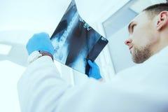 Docteur contrôlant des résultats de rayon X Photos stock