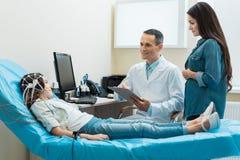 Docteur déposant des réponses de fille subissant l'encephalography Images libres de droits