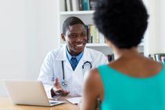 Docteur d'afro-américain avec de bonnes nouvelles pour le patient féminin photos stock