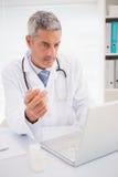 Docteur dactylographiant sur le clavier les prescriptions Images libres de droits