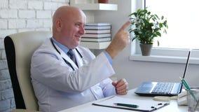 Docteur dans le Cabinet d'hôpital regardant au sourire patient et se dirigeant avec le doigt banque de vidéos