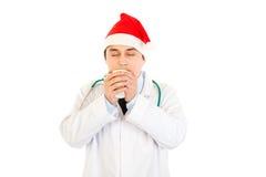 Docteur dans le chapeau de Santa appréciant la cuvette de café chaud Photos libres de droits