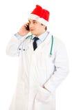 Docteur dans le chapeau du père noël parlant sur le mobile Photographie stock libre de droits