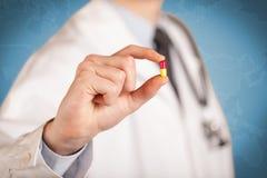 docteur dans le manteau blanc devant un mur bleu, avec un stéthoscope sur une épaule tenant une pilule entre ses doigts photos libres de droits