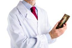 Docteur dans le manteau blanc tenant l'icône compatissante de Jésus image libre de droits