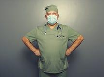 Docteur dans le masque du chirurgien au-dessus de l'obscurité Photo stock