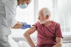 Docteur dans le masque protecteur faisant l'injection dans le bras de l'homme photo stock