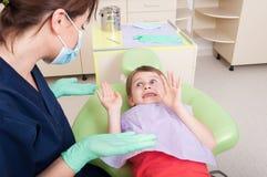 Docteur de dentiste calmant le patient effrayé d'enfant images stock