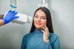 Docteur de dentiste faisant la fille patiente de dents dentaires de traitement dans le bureau dentaire photos libres de droits