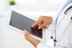 Docteur de femme à l'aide de la tablette tout en se tenant directement dans l'hôpital image libre de droits