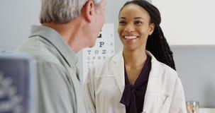 Docteur de femme de couleur parlant et étant positif avec l'aîné Photo libre de droits