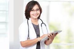 Docteur de femme âgé par milieu à l'aide de la tablette Photo libre de droits