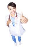 Docteur de femme renonçant à des pouces photo stock