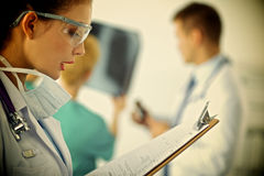 Docteur de femme se tenant avec le dossier à l'hôpital Images stock