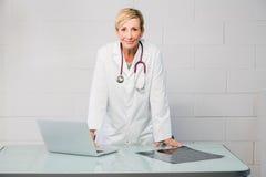 Docteur de femme se tenant derrière le bureau photographie stock libre de droits