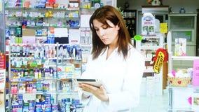 Docteur de femme travaillant avec le comprimé dans le sourire de pharmacie clips vidéos
