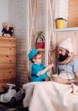 Docteur de jeu d'enfant avec l'homme à la maison, enfance Enfant dans le patient uniforme de festin de docteur Photos libres de droits