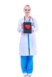 Docteur de jeune femme tenant un coeur rouge, d'isolement sur le fond blanc Images stock